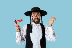 Portrait of a young orthodox Hasdim Jewish man. With wooden Grager Ratchet at Jewish festival of Purim at studio. The purim, jewish, festival, holiday stock image