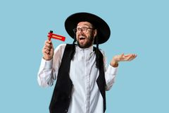 Portrait of a young orthodox Hasdim Jewish man. With wooden Grager Ratchet at Jewish festival of Purim at studio. The purim, jewish, festival, holiday royalty free stock photography