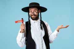 Portrait of a young orthodox Hasdim Jewish man. With wooden Grager Ratchet at Jewish festival of Purim at studio. The purim, jewish, festival, holiday stock photography