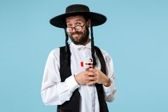 Portrait of a young orthodox Hasdim Jewish man. With wooden Grager Ratchet at Jewish festival of Purim at studio. The purim, jewish, festival, holiday royalty free stock image