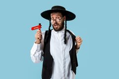 Portrait of a young orthodox Hasdim Jewish man. With wooden Grager Ratchet at Jewish festival of Purim at studio. The purim, jewish, festival, holiday stock photos