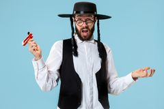 Portrait of a young orthodox Hasdim Jewish man with. Wooden Grager Ratchet at Jewish festival of Purim at studio. The purim, jewish, festival, holiday royalty free stock photography