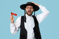 Portrait of a young orthodox Hasdim Jewish man with. Wooden Grager Ratchet at Jewish festival of Purim at studio. The purim, jewish, festival, holiday royalty free stock photos