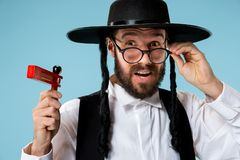 Portrait of a young orthodox Hasdim Jewish man with. Wooden Grager Ratchet at Jewish festival of Purim at studio. The purim, jewish, festival, holiday royalty free stock photo