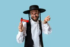Portrait of a young orthodox Hasdim Jewish man. With wooden Grager Ratchet at Jewish festival of Purim at studio. The purim, jewish, festival, holiday royalty free stock photo