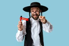 Portrait of a young orthodox Hasdim Jewish man. With wooden Grager Ratchet at Jewish festival of Purim at studio. The purim, jewish, festival, holiday royalty free stock photos