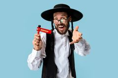 Portrait of a young orthodox Hasdim Jewish man. With wooden Grager Ratchet at Jewish festival of Purim at studio. The purim, jewish, festival, holiday stock images