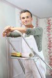 Portrait of young painter apprentice putting wallpaper royalty free stock photography