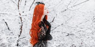 Portrait of young pale retro girl with long red hair on winter background. Beautiful redhead woman in black retro dress and with l. Ong gloves on a background of royalty free stock photos
