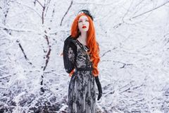 Portrait of young pale retro girl with long red hair on winter background. Beautiful redhead woman in black retro dress and with. Long gloves on a background of stock photography