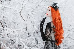 Portrait of young pale retro girl with long red hair on winter background. Beautiful redhead woman in black retro dress and with royalty free stock image