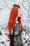 Portrait of young pale retro girl with long red hair on winter snow background. Redhead woman in black retro dress and with long stock photos