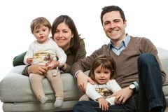 Young parents with kids on couch. Stock Image