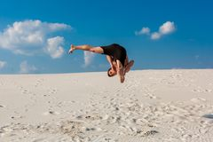 Portrait of young parkour man doing flip or somersault on the sand. Freezed moment of beginning doing bounce Stock Photo
