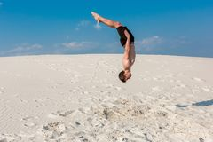 Portrait of young parkour man doing flip or somersault on the sand. Freezed moment of beginning doing bounce Stock Photos