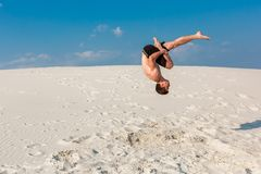 Portrait of young parkour man doing flip or somersault on the sand. Freezed moment of beginning doing bounce Stock Image