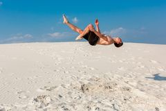 Portrait of young parkour man doing flip or somersault on the sand. Freezed moment of beginning doing bounce Royalty Free Stock Image