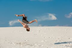 Portrait of young parkour man doing flip or somersault on the sand. Freezed moment of beginning doing bounce Royalty Free Stock Photo