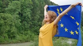 Portrait of young patriotic girl holding flag of the European Union over the sky and green forest background while. Celebrating visa-free regime, HD stock footage