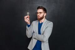 Young pensive bearded man in eyeglasses looking on bulb. Portrait of a young pensive bearded man in eyeglasses looking on bulb over black backgorund Royalty Free Stock Photo