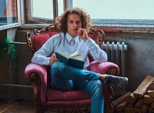 Young pensive student guy with curly hair holds a book and sitting on a chair. stock images