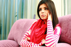 Portrait of a young pensive woman sitting on the sofa Royalty Free Stock Images
