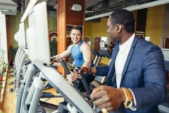 Portrait of young people with elliptic machine . Portrait of young people with elliptic machine in the gym. African men is businessman in classic suit Royalty Free Stock Photo