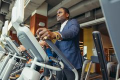 Portrait of young people with elliptic machine . Portrait of young people with elliptic machine in the gym. African men is businessman in classic suit Royalty Free Stock Photography