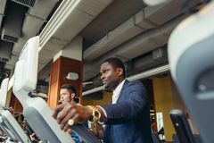 Portrait of young people with elliptic machine . Portrait of young people with elliptic machine in the gym. African men is businessman in classic suit Stock Image