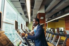 Portrait of young people with elliptic machine . Portrait of young people with elliptic machine in the gym. African men is businessman in classic suit Stock Images