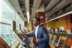 Portrait of young people with elliptic machine . Portrait of young people with elliptic machine in the gym. African men is businessman in classic suit Royalty Free Stock Photos