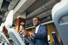 Portrait of young people with elliptic machine . Portrait of young people with elliptic machine in the gym. African men is businessman in classic suit Stock Photo