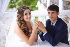 Portrait young people just married, put wedding rings on each other`s fingers, gently sit at the table and hold hands. Portrait young people just married, put Royalty Free Stock Image
