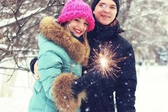 Couple lovers with sparklers happiness. Portrait of a young people in the winter Royalty Free Stock Photography