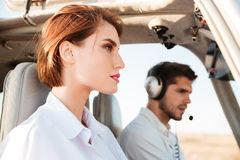 Portrait of young pilot and beautiful stewardess inside airplane cabin Royalty Free Stock Photography