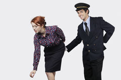 Portrait of young pilot touching flight attendant inappropriately against gray background Royalty Free Stock Photography