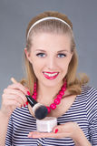 Portrait of young pinup woman with make up brush and powder Stock Photography