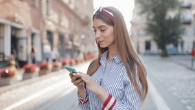 Portrait of Young Pleased Charming Woman Brown Hair Wearing Headband and Striped Dress Using her Smartphone. Girl. Looking to Camera with Beaming Smile standing stock video footage