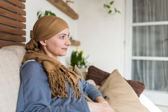 Portrait of young positive adult female cancer patient sitting in living room, smiling. Portrait of young positive adult female cancer patient sitting in living Royalty Free Stock Photos