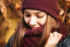 Portrait of young positive beautiful smiling girl adjusting scarf in autumn. Good mood in any weather. Royalty Free Stock Photo