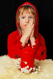 Portrait of young praying girl. Sitting   in dark room with lightning candel Royalty Free Stock Image