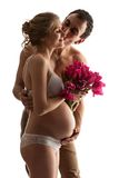 Portrait of young pregnant couple holding flowers Royalty Free Stock Image