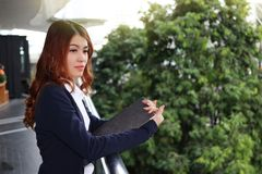 Portrait of young pretty Asian business woman holding clipboard and looking far away at public outdoor background. Stock Photos