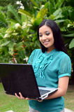 Portrait young pretty Asian muslim college girl with laptop and smile Stock Photography