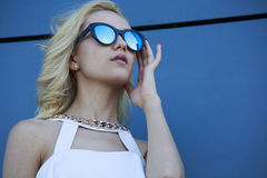 Portrait of young pretty blond model in cool mirror stylish sunglasses, Royalty Free Stock Image