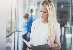 Portrait of young pretty blonde businesswoman in modern coworking studio with business team on the background.Beautiful Royalty Free Stock Photography