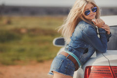 Portrait of a young pretty blonde with luxury car Royalty Free Stock Image