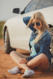 Portrait of a young pretty blonde with luxury car Stock Images