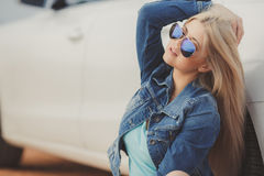 Portrait of a young pretty blonde with luxury car Royalty Free Stock Photo