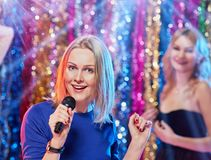Having fun at karaoke portrait. Portrait of young pretty blonde women singing at karaoke with her girlfriends Stock Images